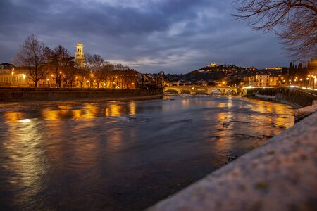 Night photo along the Adige river, Verona, Italy. Stone bridge with the bell tower of the cathedral and the sanctuary of the madonna of Lourdes.