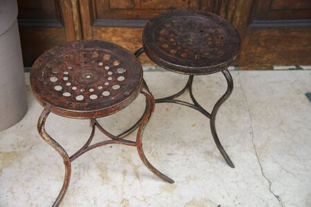 Vintage pair of old wrought iron stools.Antique wrought iron stools outside a bar.