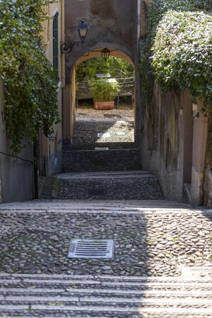 Characteristic cobbled pedestrian street to go up to the castle of Brescia, Italy.