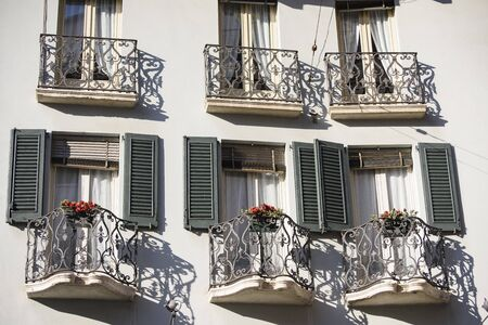 Windows and doors with small triangular shaped balcony with flowers and wrought iron railing, Brescia, Italy.