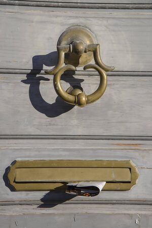 Detail of the door knocker and letter box of the wooden entrance door of a modern house in Brescia, Italy. Stock fotó