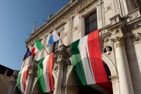 Day of the Unification of Italy and the armed forces, 4 November, Piazza della Loggia, Brescia, Italy, with tricolor flags of the Italian Republic, flag of Europe and of the city of Brescia