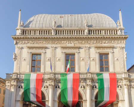 Day of the Unification of Italy and the armed forces, 4 November, Piazza della Loggia, Brescia Italy, with tricolor flags on the background of the Italian Republic.