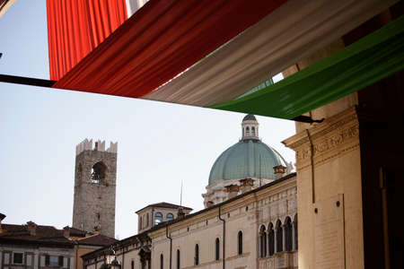 Italian flag banners, Piazza della Loggia, Brescia, Italy. In the background the dome of the cathedral and the Pegol tower.