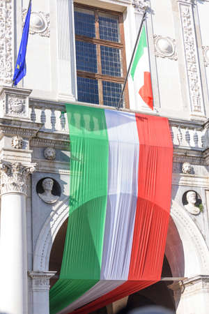 Tricolor flag of the Italian Republic, with flag of Europe and the city of Brescia, Italy. Palace in Piazza della Loggia, day of the unification of Italy and the armed forces.