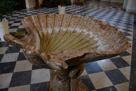 Old holy water stoup in the shape of a shell in the church of San Francesco in Brescia, Italy.