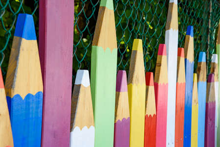 Outdoor fence in the shape of colored pencils. Pointed wooden poles of various heights colored in multicolor in the shape of a pencil.