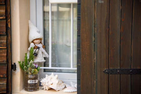 Window with vintage items on the windowsill. Rag doll and jar with coffee inscription.