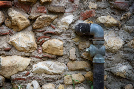 Detail of a gas pipe outside a house with a stone wall.