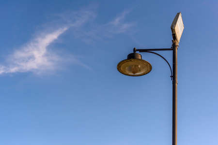 Street lamp with two types of lamps, vintage and modern spotlight. Blue sky background with copy space. Archivio Fotografico