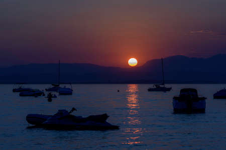 Fiery red sky at autumn sunset at Lake Garda, Italy. Rowing boats and speedboats in silhouettes.