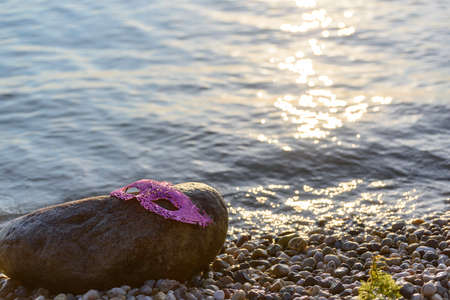 Pink glitter mask forgotten on a stone by the lake. Rays of light on the water and on the stones of the shore.