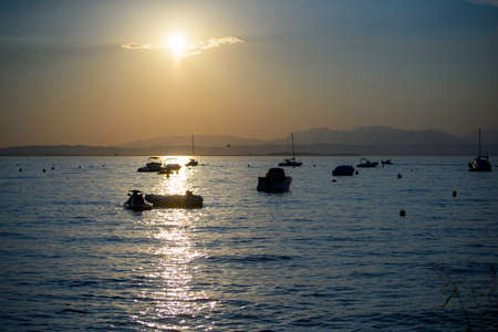 Yellow sky at autumn sunset over Lake Garda, Italy. Rowing boats and speedboats in silhouettes.