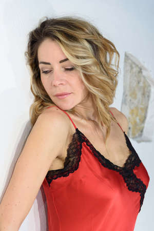 Close-up of blonde girl in red petticoat in silk lingerie. Single woman. White background. Archivio Fotografico
