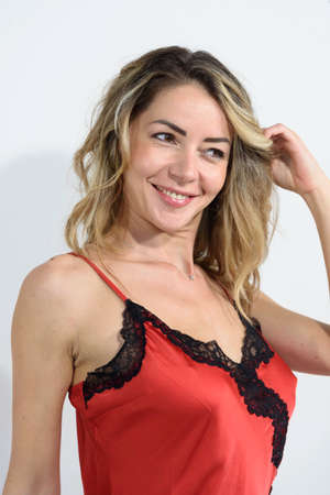 Close-up of blonde girl in red petticoat in silk lingerie. Single smiling woman looking at the camera. White background. Copy space. Archivio Fotografico