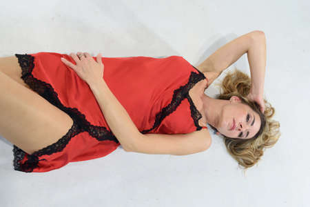 Full length of blonde girl in red petticoat in silk lingerie. Single woman lying on the ground. White background. Copy space.