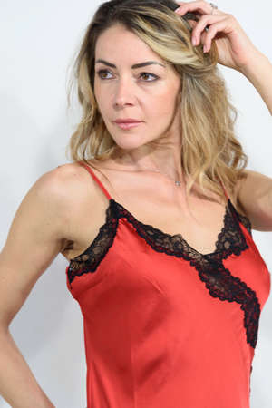 Close-up of blonde girl in red petticoat in silk lingerie. Single woman looking at the camera. White background. Copy space.