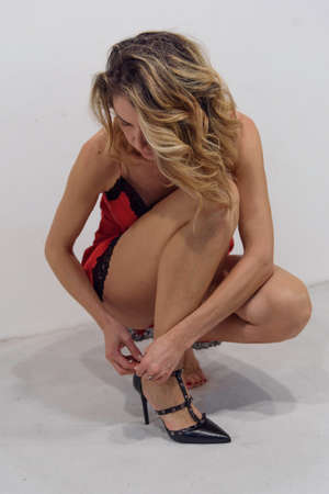 Kneeling girl tying her shoes. Single blond woman in red petticoat on a white background.