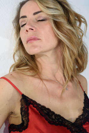 Close-up of blonde girl with closed eyes in red petticoat in silk lingerie. Single woman. White background. Archivio Fotografico