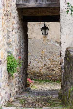 Old houses in Oneta, Bergamo, Italy. Most beautiful villages in Italy. Tricolor flag on balcony.