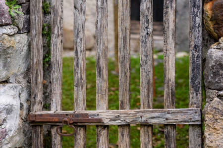 Detail of old wooden gate with metal lock. Detail vintage object in the countryside.