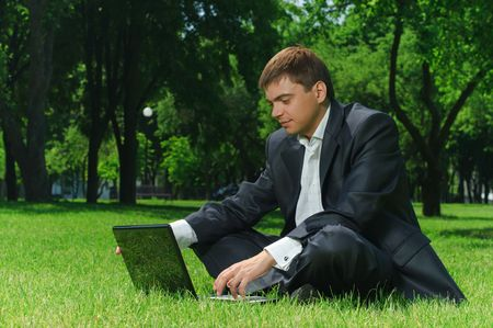 Young successful businessman resting in a park on the grass looking at the latest news on the Internet