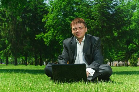 Young successful businessman resting in a park on the grass photo