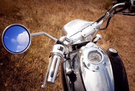 reflection of blue sky and clouds in the rearview mirror motorcycle Stock Photo