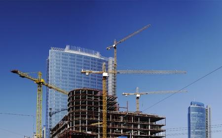 Bouwplaats met hoog kranen op achtergrond van moderne kantoorgebouwen
