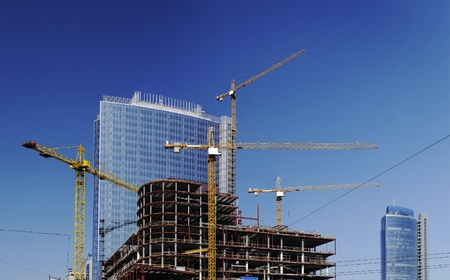 Construction site with tall cranes on background of modern office buildings photo