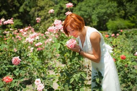 Mooie jonge vrouw in een tuin van rozen op zonnige zomerdag