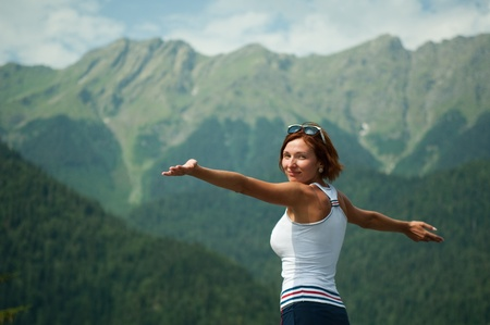 rejoices: beautiful young girl in mountains rejoices  the space of freedom Stock Photo