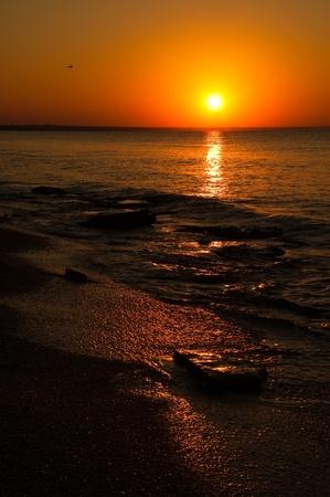 Surf op de golven op een verlaten strand met een oranjerode zonsondergang
