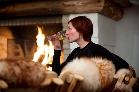 beautiful young woman relaxing and drinking wine in a cozy house with fireplace photo