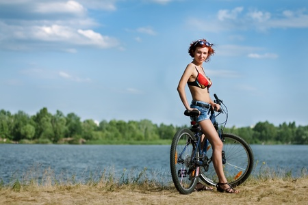 beautiful young woman on a bicycle at the background of the river and the blue sky photo