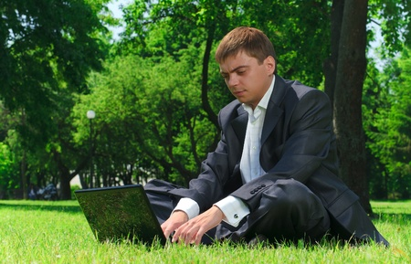 Young successful businessman resting in a park on the grass looking at the latest news on the Internet photo