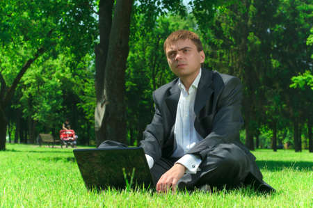 Young successful businessman resting in a park on the grass working on a laptop photo