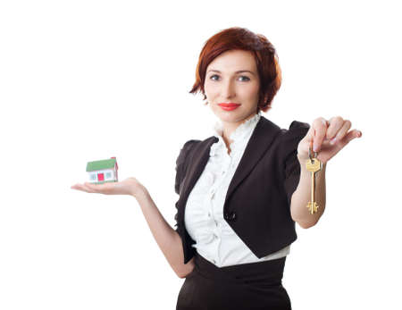 Beautiful young woman holding keys and house model over white - real estate loan concept photo
