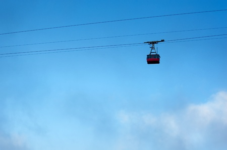 ski lift is moving up high in the sky above the clouds