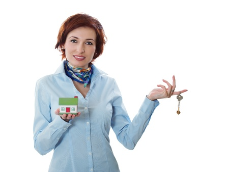Beautiful young woman holding keys and house model over white - real estate loan concept 스톡 콘텐츠
