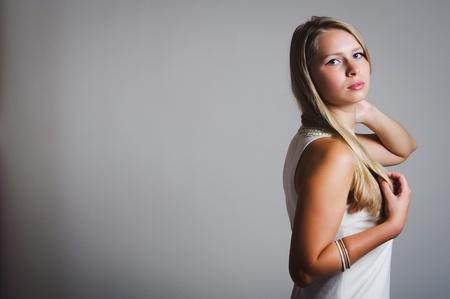 Portré fiatal, vonzó nő a szürke háttér.