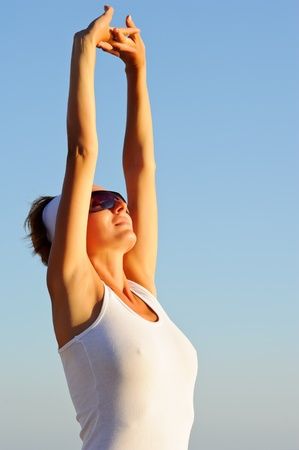 Smiling girl with arms raised towards the sky on sunny day on sunrise photo