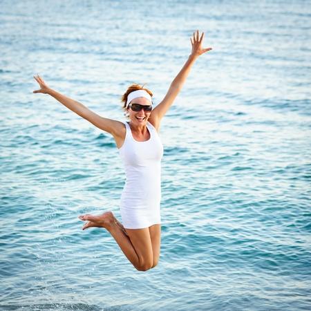 Boldog fiatal nő ugrás a strandon Stock fotó