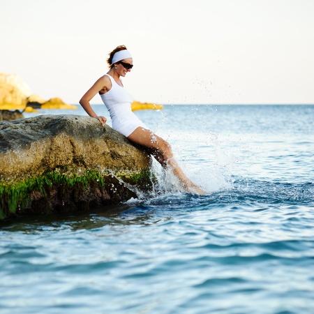 Gyönyörű nő ül egy kő és fröccsenő a tengerben Stock fotó