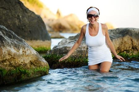 Gyönyörű nő fröccsenő a tenger közelében kövek