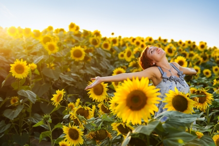 young beautiful woman on blooming sunflower field in summer photo