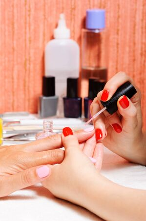 Skin and nail care. Applying of the Transparent varnish. photo
