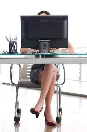 secretaria: niña sentada en su lugar de trabajo detrás de una pantalla de ordenador