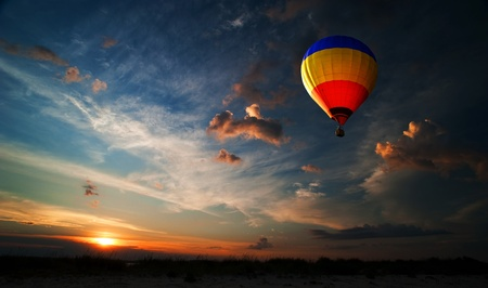 Colorful hot air balloon is flying at sunrise photo