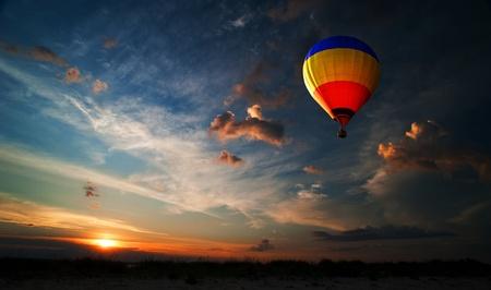 Kleurrijke hete luchtballon vliegt bij zonsopgang Stockfoto